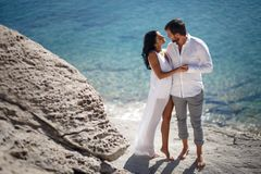 Perfect couple portrait, standing on stone beach behind mediterranean sea, honeymoon in Greece. stock images