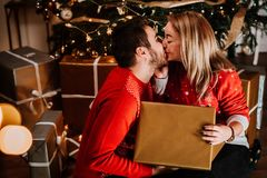 Couple wearing red sweaters, kissing and opening santa presents on Christmas morning royalty free stock photography