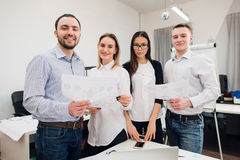 Perfect creative team. Group of four cheerful young people looking at camera with smile while leaning to the table in Stock Photography