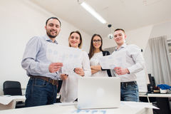 Perfect creative team. Group of four cheerful young people looking at camera with smile while leaning to the table in Royalty Free Stock Images