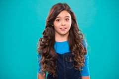 Perfect curling hair. Teaching healthy hair care habits. Kid girl long healthy shiny hair. Kid happy cute face with. Adorable curly hairstyle stand over blue royalty free stock photo