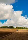 Perfect day for agriculture. Somewhere in Zeeland, Denmark, the field is being ploughed under a perfect mid-day sky Stock Image