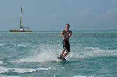 Perfect Day in Aruba Riding a Wakeboard on the Ocean. Young guy riding a wakeboard on the ocean off of Aruba Stock Image