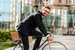Perfect day for cycling to work. Side view of cheerful young businessman looking at camera and smiling while riding on his bicycle Stock Photo