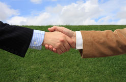 Perfect Deal. Two business men making a deal with a handshake at the field Royalty Free Stock Images