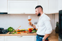 Perfect dinner. Confident male sommelier looking at wine glass standing in modern kitchen and cooking salad. Details of perfect dinner. Confident male sommelier Royalty Free Stock Photos