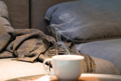 Perfect evening - cozy sofa, warm blanket and a Cup of fragrant hot coffee. A cozy warm evening with fragrant hot coffee, cozy sofa and warm blanket. Interior stock photos