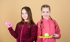 Perfect in every way. Happy children with sport equipment. Little girl. Fitness barbell. gym workout of teen girls. Tennis racket and ball for activity. Sport stock image