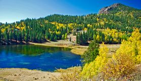 Beautiful Mountain Landscape With Lake Pines and Aspens in the Fall. This is a perfect fall day in the Rocky Mountains replete with a lake, pines and aspens Stock Image