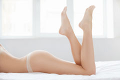 Perfect female body. Cropped image of beautiful women lying on f Royalty Free Stock Photo