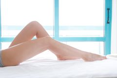 Perfect female legs on bed with bent knees side view. Cropped image of erotically lying on bed woman in bedroom. Copy space,. Top view, mock up royalty free stock photo