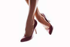 Perfect female legs with red high heels on white background. Female legs with red high heels isolated on white background Stock Images