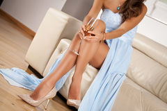 Perfect female legs wearing high heels. Perfect lady legs wearing high heels. Woman drinking champagne. Holidays and relaxation concept royalty free stock image
