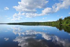 Perfect Finnish lake scenery. With white clouds reflecting from calm clear water stock image