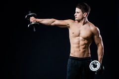 Perfect fit athletic guy posing with barbell plate in gym, perfect lat muscle, shoulders, biceps, triceps and chest Royalty Free Stock Photography
