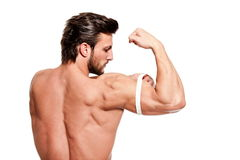 Perfect fit man. Handsome fit young man measuring his arm with centimeter Royalty Free Stock Image