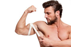 Perfect fit man. Handsome fit young man measuring his arm with centimeter Royalty Free Stock Photo