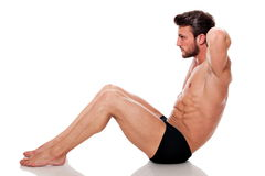 Perfect fit man. Young fit man, training his abs: crunch, on white background Royalty Free Stock Photos