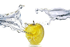 Perfect fresh water splash on yellow apple isolate Stock Images