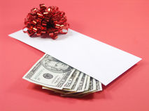 The perfect gift (red). Envelope with US twenty dollar bills and a red bow isolated on red. shallow depth of field. focus on money Royalty Free Stock Photos