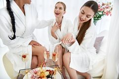 Happy girls in bathrobes celebrating friend engagement at spa stock image