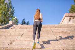 A perfect girl with charming long light hair is climbing up the stairs. A beautiful lady in leggings, a top and blue trainers. stock images