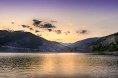 Perfect golden hour over reflective lake and horizon rocky mountains royalty free stock photography