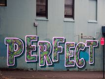 `Perfect`, Graffiti  Painted on Blue Wall Royalty Free Stock Image