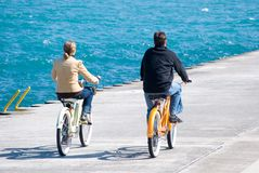 Perfect harmony. Couple is riding their bikes along lake shore in a perfect harmony Royalty Free Stock Images