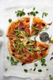 Pizza with tomato sauce, prosciutto and arugula. Perfect healthy lunch idea: Pizza with tomato sauce, prosciutto and arugula royalty free stock photo