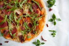 Pizza with tomato sauce, prosciutto and arugula. Perfect healthy lunch idea: Pizza with tomato sauce, prosciutto and arugula royalty free stock image