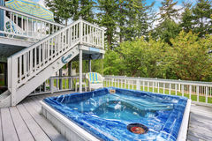 Perfect hot tub on gray deck of modern home. Stock Images