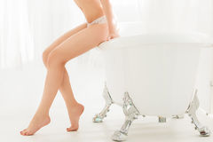 Perfect legs of woman sitting on bathroom side Stock Images