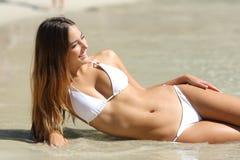 Perfect lichaam van een vrouw in bikini die op het strand liggen royalty-vrije stock afbeeldingen