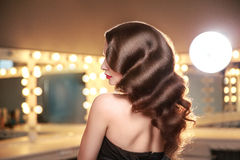 Perfect long curly hair. Back, side view. Brunette in makeup room with studio lights. Stock Image