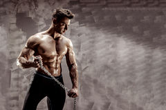 The Perfect male body - Awesome bodybuilder posing. Hold a chain with tattoo Stock Photo