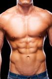 Perfect male torso. Close-up of young muscular man with perfect torso standing against black background Royalty Free Stock Images