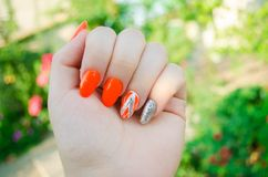 Perfect manicure and natural nails. Attractive modern nail art design. orange autumn design. long well-groomed nails royalty free stock photo
