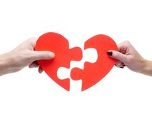 Perfect match. Male and female hand matching red jigsaw heart halves over white background Stock Images