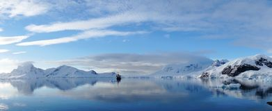 Perfect mirror reflections of snowy mountains and icebergs in Antarctica. Stock Photos