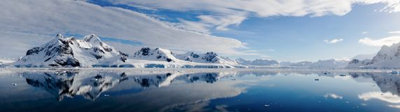 Perfect mirror reflections of snowy mountains and icebergs in Antarctica. stock photography