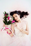 Perfect Model Girl with Flower Arrangement. Curly Hairstyle and Makeup  Lying on White. Top View Stock Photo