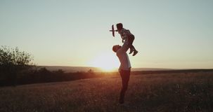 Perfect moments dad with his son , at sunset playing together with a airplane , boy dreaming will becoming a pilot. shot. Perfect moments dad with his son , at stock footage
