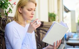 Perfect morning concept. Mug coffee and interesting book best combination perfect weekend. Woman have drink cafe terrace. Outdoors. Girl drink coffee while read royalty free stock images