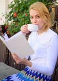 Perfect morning concept. Woman have drink cafe terrace outdoors. Mug of good coffee and interesting book best. Combination for perfect weekend. Girl drink royalty free stock photography