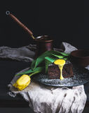 Perfect morning set for woman. Piece of truffle chocolate cake with lemon curd icing, hot coffee and yellow tulip on dark backdrop Stock Photography
