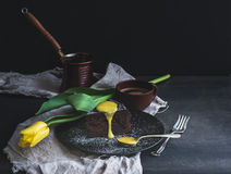 Perfect morning set for woman. Piece of truffle chocolate cake with lemon curd icing, hot coffee and yellow tulip on dark backdrop Royalty Free Stock Photo