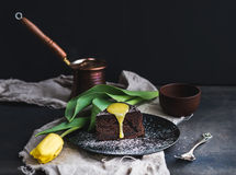 Perfect morning set for woman. Piece of truffle chocolate cake with lemon curd icing, hot coffee and yellow tulip on dark backdrop. Perfect morning set for woman Stock Photography