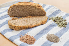 Perfect nut and seeds bread with pumpkin, flax and chia seeds on a kitchen cloth. Tasty and healthy paleo gluten free and yeast free bread can be used in every stock image
