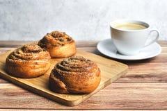 Perfect ontbijt van eigengemaakte kaneelbroodjes en koffie op houten lijst Rustieke stijl royalty-vrije stock afbeelding